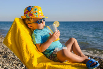 Boy kid in armchair with juice glass on beach against sea